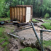 (Brad Davis/The Register-Herald) Owens Branch resident Ben Eastman's home in the aftermath of Thursday's flooding. His shed, fully loaded with equipment, tools and all is turned over with it's former resting place washed out.