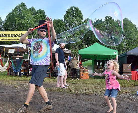 (Brad Davis/The Register-Herald) Four-year-old Aubree Gill has a blast busting massive bubbles produced by a merry, top hat-wearing fellow Friday evening at Mountian Music Festival.