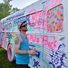 (Brad Davis/The Register-Herald) Snowshoe Mountain resident Kevin Sprecher adds to an old school bus on hand as a massive public art canvas parked in the main stage area of the Mountain Music Festival Friday evening at the Mountain Music Festival inside Ace Adventure Resort.