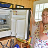 (Brad Davis/The Register-Herald) Abraham resident Pam Helmandollar shows off her primary source of drinking water, a small refrigerator that holds the two, 36-count packages of bottles she purchases at the store every week during a Register-Herald visit to the area June 2.