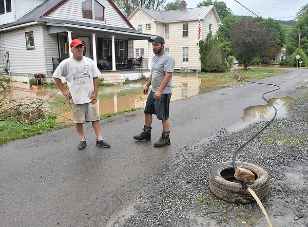 (Brad Davis/The Register-Herald) Residents began pumping flood waters from their homes as it began to recede in Alderson Friday evening.