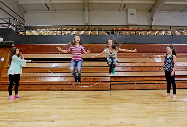 """Jessica Dial, center left, 11, and Savannah Bigham, center right, 12, jump rope together as Ashlee Taylor, left, 12, and Hannah Hunter, right, 12, turn the rope during Fayetteville Elementary's """"Jump Rope For Heart"""" at the Soldier's and Sailors Memorial Building in Fayetteville on Friday. Fayetteville Elementary aimed to raise over $2,000 for the American Heart Association's fight against heart disease. (Chris Jackson/The Register-Herald)"""
