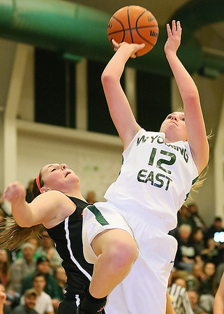 (Brad Davis/The Register-Herald) Wyoming East's Misa Quesenberry drives to the basket as PikeView's Kaleigh Peyton defends during the Lady Warriors' regional championship victory over the Panthers Friday night in New Richmond.