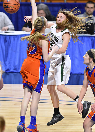 (Brad Davis/The Register-Herald) Wyoming East's Gabby Lupardus dishes to an open teammate as Tolsia's Sarah Jude defends during the Lady Warriors' first round win over the Rebels in the state basketball tournament Wednesday evening at the Charleston Civic Center.