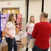 Anyah Brown, 12, front left, and Chloie Lilly,12, both students at PikeView Middle School, show their social studies fair project about the difference between generic and name brand prescription drugs to judges Wesley Young, right, and Chris Weaver during the social studies fair at the Beckley-Raleigh County Convention Center in Beckley on Saturday. (Chris Jackson/The Register-Herald)