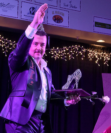 Contestant Scott Parker waves to the crowd after being named top hunk at the conclusion of the Women's Resource Center's Hunks in Heels event Friday night at the Beckley-Raleigh County Convention Center.
