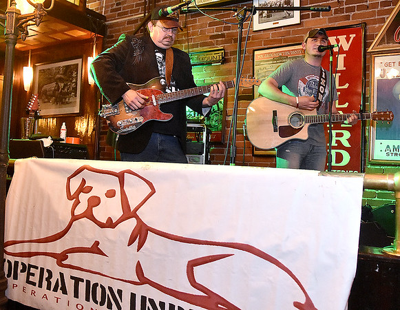Country singer Gabe Dixon, right, and fellow guitarist Larry Davis Jr. jam out as they perform during Operation Underdog's annual Wagfest fundraising event Saturday night at Foster's Main Street Tavern.