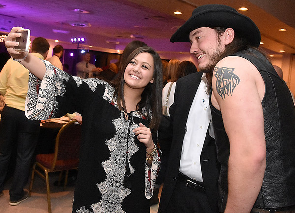 Contestant Cody Wickline gets photos taken with fans during the mixer portion of the Women's Resource Center's Hunks in Heels event Friday night at the Beckley-Raleigh County Convention Center.