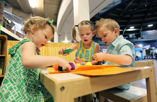 Siblings Lucy, 2, Liam and Annie, 4, Wilson work on a tree study with Ghent Elementary's booth during the Raleigh County Pre-K Expo at the Beckley-Raleigh County Convention Center on Wednesday. (Chris Jackson/The Register-Herald)