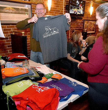 Washington, D.C. resident Don Strawder holds up an Operation Underdog shirt he purchased during the animal rescue organization's annual Wagfest fundraising event Saturday night at Foster's Main Street Tavern as his wife Nora, right, browses other items. The couple frequently meets the group in their area as part of a network of dedicated volunteers who help to transport rescue animals around the country.