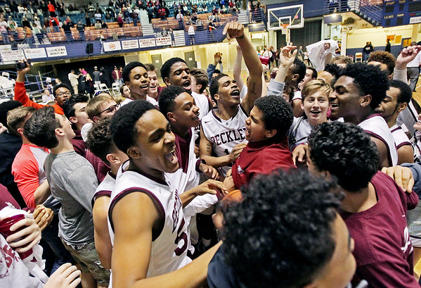 The Woodrow Wilson basketball team is engulfed by the student section following their regional AAA final victory against Ripley at the Beckley-Raleigh County Convention Center in Beckley on Tuesday. (Chris Jackson/The Register-Herald)