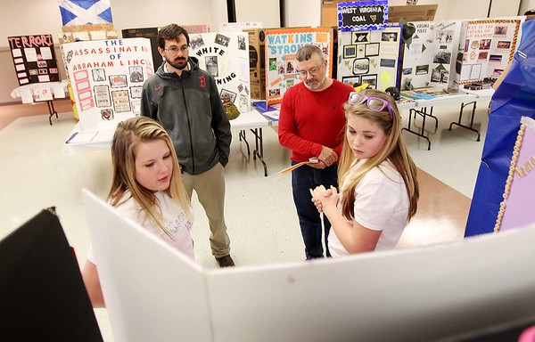 Chloie Lilly, 12, front left, and Anyah Brown, 12, both students at PikeView Middle School, show their social studies fair project about the difference between generic and name brand prescription drugs to judges Wesley Young, back left, and Chris Weaver during the social studies fair at the Beckley-Raleigh County Convention Center in Beckley on Saturday. (Chris Jackson/The Register-Herald)