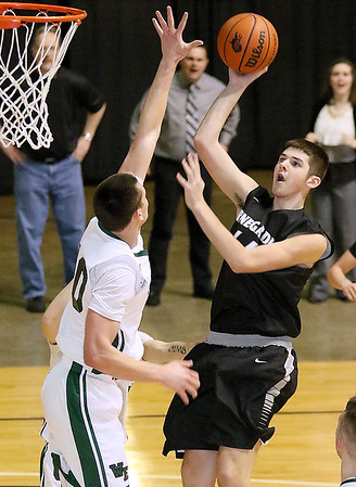 (Brad Davis/The Register-Herald) Westside's Corey Hatfield drives to the basket as Wyoming East's David Carte defends during the Renegades' win over the Warriors Saturday night at the Beckley-Raleigh County Convention Center.