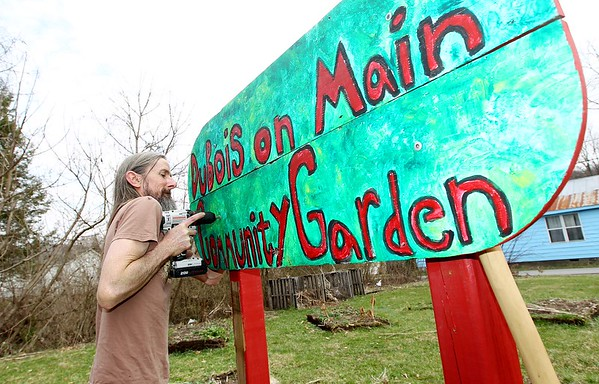 Jim Withem, from Mt. Hope, works fro take down the DuBois on Main Community Garden sign in Mt. Hope on Saturday. The garden is being moved to another location in Mt. Hope. (Chris Jackson/The Register-Herald)