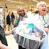 Debra Whitt, education coordinator, left, and Mike Burton, district manager, presented Cassie Newman, of Beckley with a large gift basket for being the 100th costomer during the grand opening of JoAnn Fabrics and Crafts at the former location of the Raleigh Mall in Beckley Thursday morning.<br /> Rick Barbero/The Register-Herald