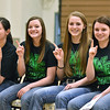 (Brad Davis/The Register-Herald) Wyoming East players (from left) Haley Butcher, Kaytlin Daniels, Kara Sandy and Krista Hagy hold up number 1's as fans and family take photos during the opening moments of a ceremony celebrating the Lady Warriors' first ever girls basketball state championship Monday evening in the school's gymnasium.