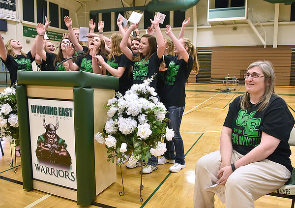 (Brad Davis/The Register-Herald) Wyoming East head coach Angie Boninsegna, right, looks to the crowd with a smile as her singing Lady Warriors perform one of their now famous routines at the conclusion of a ceremony celebrating the school's first ever girls basketball state championship Monday evening in the school's gymnasium.