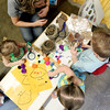 Siblings Lucy, 2, Liam and Annie, 4, Wilson work on a tree study with Ghent Elementary's booth as pre-school teacher Sara Haye instructs during the Raleigh County Pre-K Expo at the Beckley-Raleigh County Convention Center on Wednesday. (Chris Jackson/The Register-Herald)
