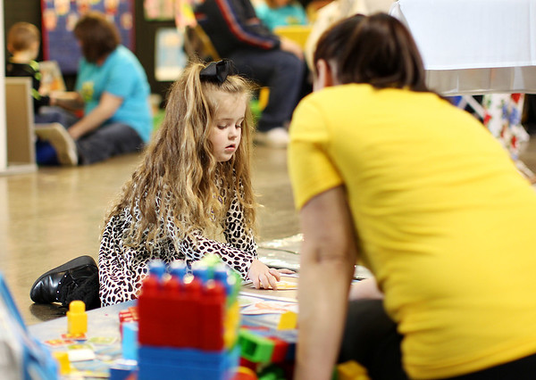 Aubrei Denny, 4, works on a puzzle with Busy Bee Child Care's Amanda Thompson during the Raleigh County Pre-K Expo at the Beckley-Raleigh County Convention Center on Wednesday. (Chris Jackson/The Register-Herald)