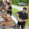 (Brad Davis/The Register-Herald) Reverend Rey Candicho, lower right, and others begin to fill their plates during the annual Memorial Day picnic at the 140-year-old Sacred Heart Catholic Church in Meadow Bridge Sunday afternoon.