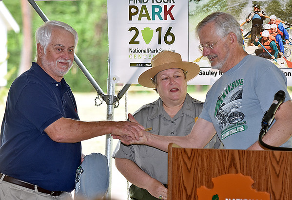 (Brad Davis/The Register-Herald) Trish Kicklighter (middle), Superintendent of three different parks along the New River Gorge National River, looks on as Dr. Jerry Beasley (right), President Emeritus of Concord University, thanks his colleague Dr. Doug Machesney, left, for all his help in making Camp Brookside's reopening possible during a ceremony Saturday afternoon in Brooks.
