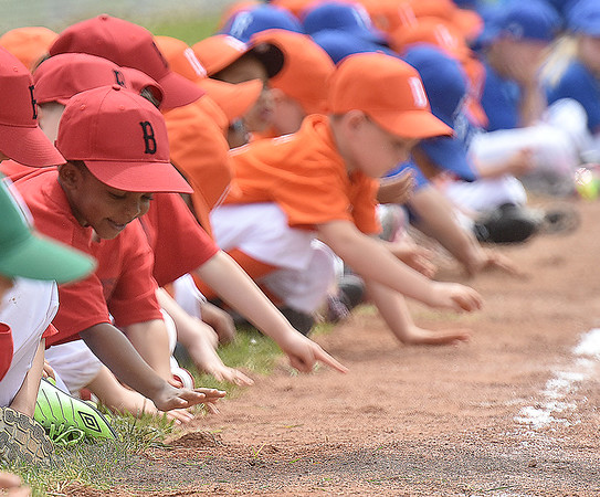 (Brad Davis/The Register-Herald) Restless young teeball players pass the time by playing in the infield dirt while hundreds of other players, coaches and families line up on the Beckley Little League field during an opening day ceremony for the teeball league Saturday afternoon.