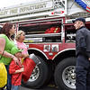 (Brad Davis/The Register-Herald) Beckley firefighter Scott Datsko, right, shows off one of Beckley Fire Department's ladder trucks and answers questions from five-year-old Jaxon Webb, his mother Catie and Elizabeth Gray about all the specialized gear it carries during a Disaster Preparedness Fair Saturday morning at Woodrow Wilson High School.