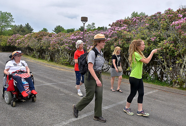 (Brad Davis/The Register-Herald) National Park Service guide Abby Adkins, middle, leads a group consisting of Beth Stanley, left, London, Canada resident Ruth Lalonde (2nd from right), Active Southern West Virginia's Becka Lee, right, and her mother Ruth Ann Lee (background 2nd from left) on Rhododendron Walk through Grandview Park Sunday afternoon.