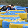 (Brad Davis/The Register-Herald) Toronto, Canada resident Steven Liu, right, tries to sabotage the efforts of his friend Bay Bahri, left, as he tries navigate a floating pathway during Ace Adventure Park's opening day Saturday morning in Minden.