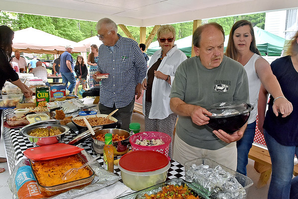 (Brad Davis/The Register-Herald) Church member Rusty Burwell, 2nd from right, helps prepare the feast during the annual Sacred Heart Catholic Church Memorial Day picnic in Meadow Bridge following mass Sunday afternoon. The church itself has been in service for 140 years and the annual picnic has been going on every year for almost as long.