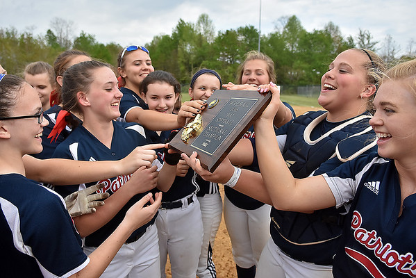 (Brad Davis/The Register-Herald) Independence players reach in to get a precious touch on the championship plaque after the Patriots defeated the Liberty Raiders to take the sectional title Saturday afternoon in Coal City.