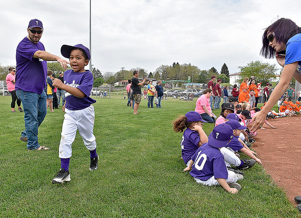 (Brad Davis/The Register-Herald) Young teeball player Elijah Petrey (left) is so excited that he almost runs past his Torches teammates while coach Lucas Pugalee, left and parent Ashlee Belcher, right, tell him where line up on the Beckley Little League field during an opening day ceremony for the teeball league Saturday afternoon. Pictured with Petrey are teammates (left to right), Blake Pugalee, Logan Crouse, Kaleb Stewart and Aliyah Fleming.