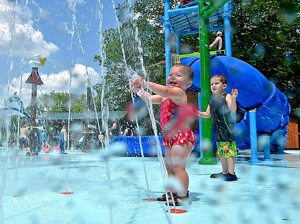(Brad Davis/The Register-Herald) Water flies everywhere as one-year-old Audrey Kennedy, middle, reaches into a giant sprinkler shooting water from the ground inside the new Splash Park at Lake Stephens Saturday afternoon.