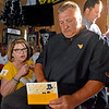 (Brad Davis/The Register-Herald) Men's basketball coach Bob Huggins signs a birthday card brought to him by fan Barb Slone that will then be sent to 94-year-old Parkersburg resident Winnie Flanagan as a gift during the opening moments of the annual WVU Coaches Caravan Wednesday evening at Calacino's.