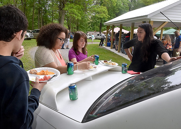 (Brad Davis/The Register-Herald) No table space is no problem for (from left) Evan Epstein (back turned), Sarah Runty, Kimberly Treadway and Katherine Spence, who simply use the back of a car during the annual Memorial Day picnic at the 140-year-old Sacred Heart Catholic Church.