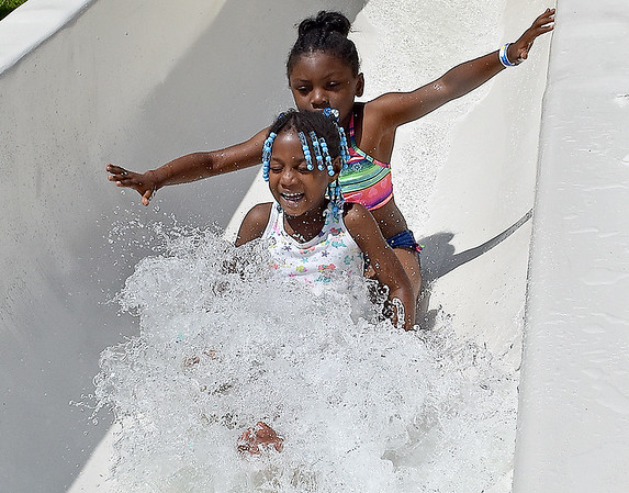 (Brad Davis/The Register-Herald) Seven-year-old Gvonni Lewis (back) and five-year-old Janeeya Thompson (front) speed down the waterslide during opening day at the New River Park pool Saturday afternoon.