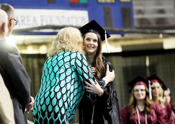 Hannah Ballengee, 17, a student at Shady Spring High School and enrolled in ACT's Careers in Education receives a hug from ACT Instructor Drema McNeal after receiving her diploma during ACT's annual commencement Thursday, May 18, 2016, at The Beckley Raleigh County Convention Center in Beckley.(Chris Jackson/The Register-Herald)