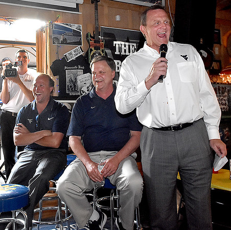 (Brad Davis/The Register-Herald) Athletic Director Shane Lyons, right, has a few laughs while speaking as he, football coach Dana Holgorsen (left) and women's basketball coach Mike Carey enjoy the atmosphere during the opening moments of the annual WVU Coaches Caravan Wednesday evening at Calacino's.