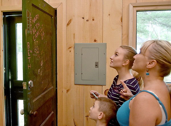 (Brad Davis/The Register-Herald) Beth Fish, far right, shows her children Shelby Jarvis, middle, and Lewis Fish all the signatures still visible on the doors inside the renovated cabins at the historic and newly revitalized Camp Brookside Saturday afternoon in Brooks near Hinton. Fish was married at the camp in 1990, and the door still bears her name on it, visible on the left side of the door near the middle.