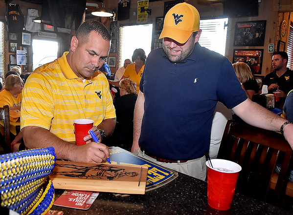 (Brad Davis/The Register-Herald) Beckley resident Anthony Johnson gets some memorabilia signed by football defensive coordinator Tony Gibson during the opening moments of the annual WVU Coaches Caravan Wednesday evening at Calacino's.