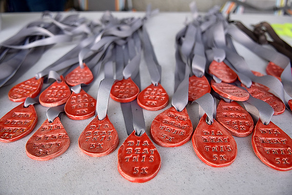 "(Brad Davis/The Register-Herald) Special medallions shaped like drops of blood with the word ""Dia-Beat-This"" await participants of the 5K Glow Walk/Run to raise awareness for juvenile diabetes Friday night at the YMCA Paul Cline Memorial Sports Complex."