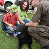 (Brad Davis/The Register-Herald) Five-year-old Jaxon Webb and his mother Catie meet Beckley Police Department K-9 Helo, active-duty partner to officer Will Reynolds, right, during a Disaster Preparedness Fair Saturday morning at Woodrow Wilson High School.