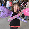 (Brad Davis/The Register-Herald) Seven-year-old Beckley resident Cailyn Humphrey manages to hold onto the two giant infaltable lollipops as she chomps down on a cupcake from The Bake Shoppe during the Sweet Treats Dessert Festival Saturday afternoon inside the Intermodal Gateway.