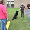 (Brad Davis/The Register-Herald) Area residents look on as Beckley Police officer Will Reynolds describes some of the techniques he uses to communicate with K-9 Helo during a Disaster Preparedness Fair Saturday morning at Woodrow Wilson High School.
