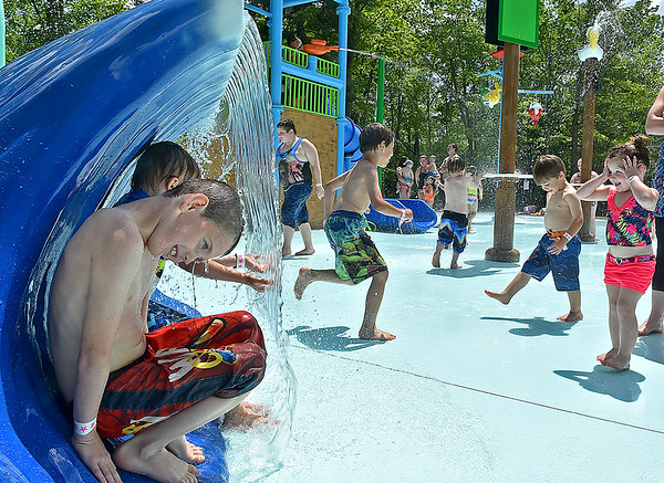 (Brad Davis/The Register-Herald) Eight-year-old Oak Hill resident Hayden Lokant, nearest left, hides behind a wall of water as he and a swarm of other youngsters enjoy the brand new Splash Park at Lake Stephens Saturday afternoon.