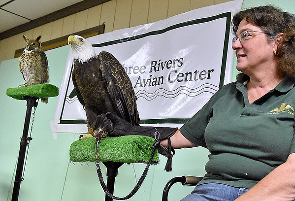 (Brad Davis/The Register-Herald) Three Rivers Avian Center executive director Wendy Perrone stands by to answer any questions passing visitors might have about Regis the bald eagle or Hoolie the great horned owl, who both sit next to her during a Spring Migration Celebration Saturday morning at Little Beaver State Park. TRAC brought veteran travelers Regis and Hoolie along with a couple of other raptors along to the annual event, which also featured educational games and activities designed to teach kids the importance of all of nature's creatures.
