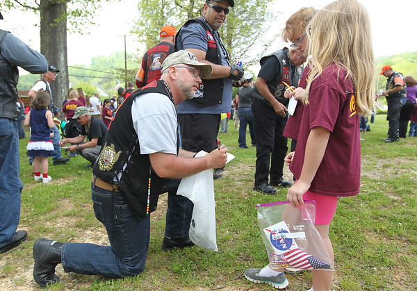 Daniel Slocum, left, from Olympia, Wa., and is retied Army, since his autograph for Lyssa Bennett and Kallie O'Dell, both students at Rainelle Elementary, during the annual Run for the Wall Thursday. (Chris Jackson/The Register-Herald)