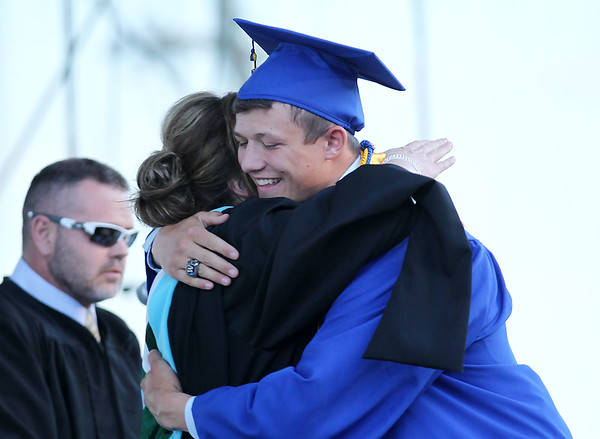 Greenbrier West's Caleb Kearns smiles as he hugs Principal Amy Robertson during their Class of 2016 graduates Friday at the State Fairgrounds in Fairlea. (Chris Jackson/The Register-Herald)