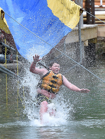 (Brad Davis/The Register-Herald) 10-year-old Charleston resident Colin Pritt is barely visible through a cascade of water, splashes down into the lake after a high speed run down giant slide during Ace Adventure Park's opening day Saturday morning in Minden.