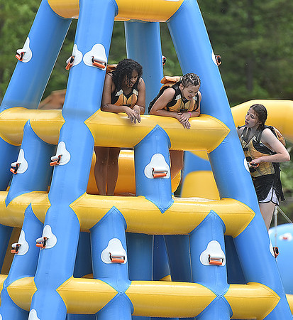 (Brad Davis/The Register-Herald) Swimmers enjoy the view from one of the taller floating toys on the lake during Ace Adventure Park's opening day Saturday morning in Minden.